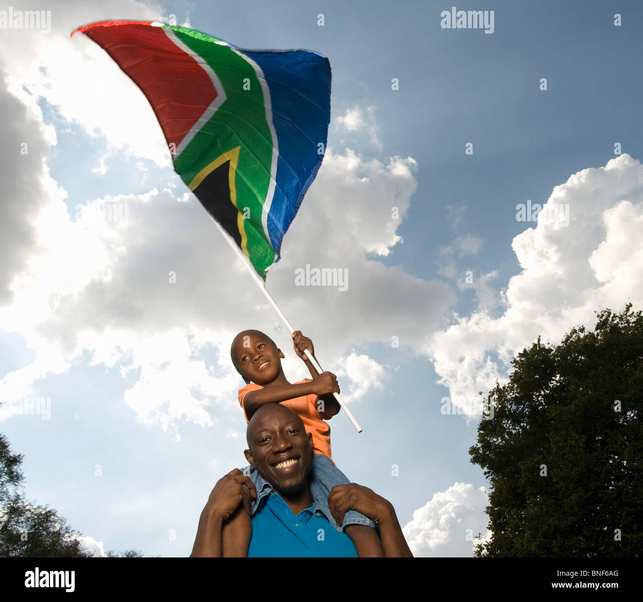 Father carrying son (4-5) on shoulders, waving South African Flag, Johannesburg, Gauteng Province, South Africa - Stock Image