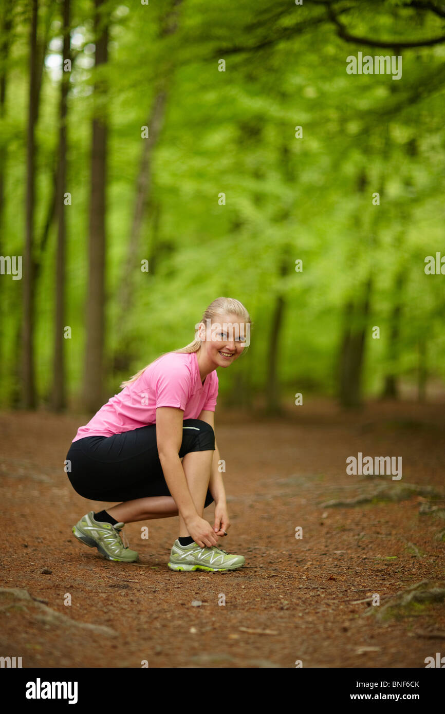 Woman running, tying laces - Stock Image