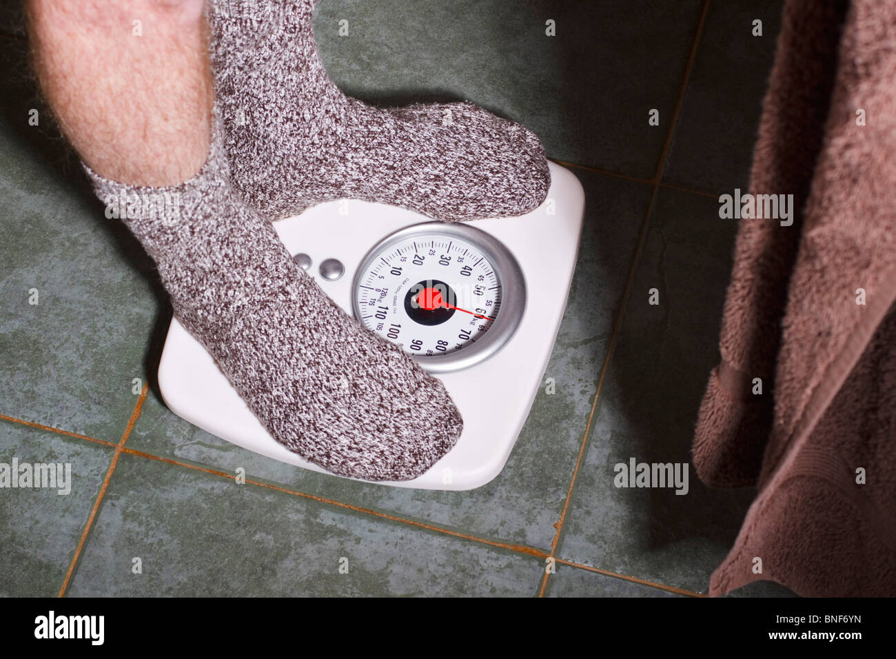 Man in socks weighing himself on a bathroom scale. Stock Photo