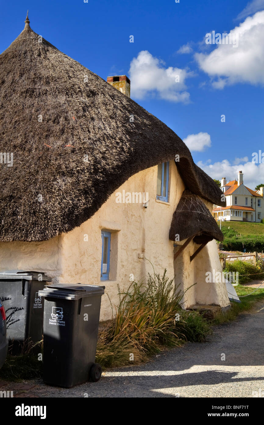 Thatched roof cottage in Hope Cove, South Hams, Devon. Wheeled dustbins are an unattractive modern intrusion. - Stock Image