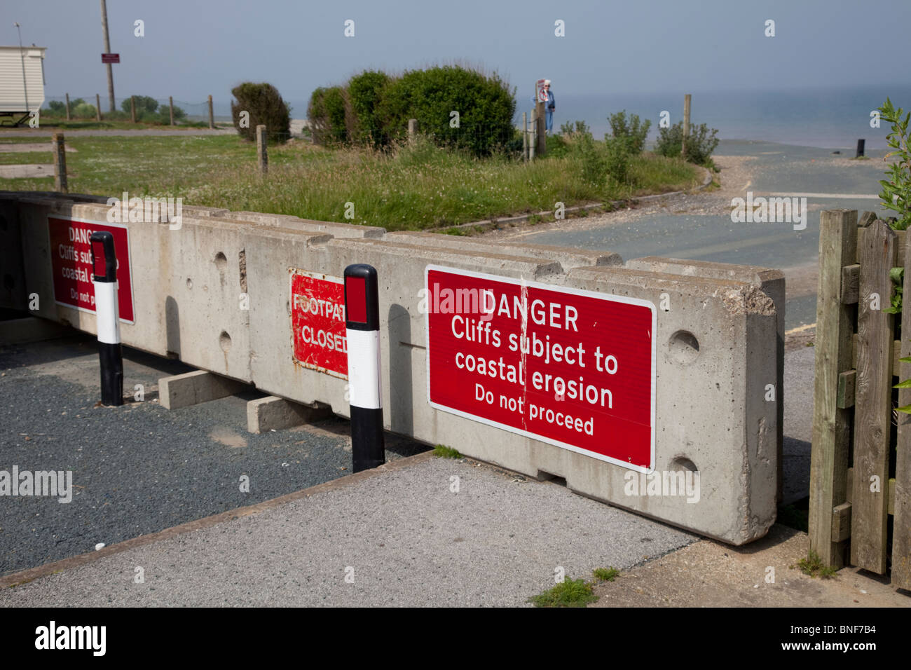 Danger collapsing cliffs signs on blocked coast road Skipsea East Riding of Yorskhire UK - Stock Image