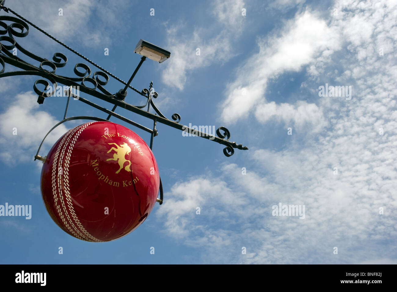 The cricket ball suspended against a Summer blue sky is the hanging pub sign of the Long Hop public house in Meopham - Stock Image