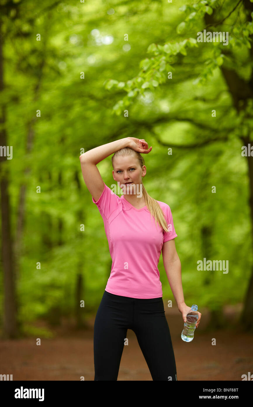 Woman running, standing still with water - Stock Image