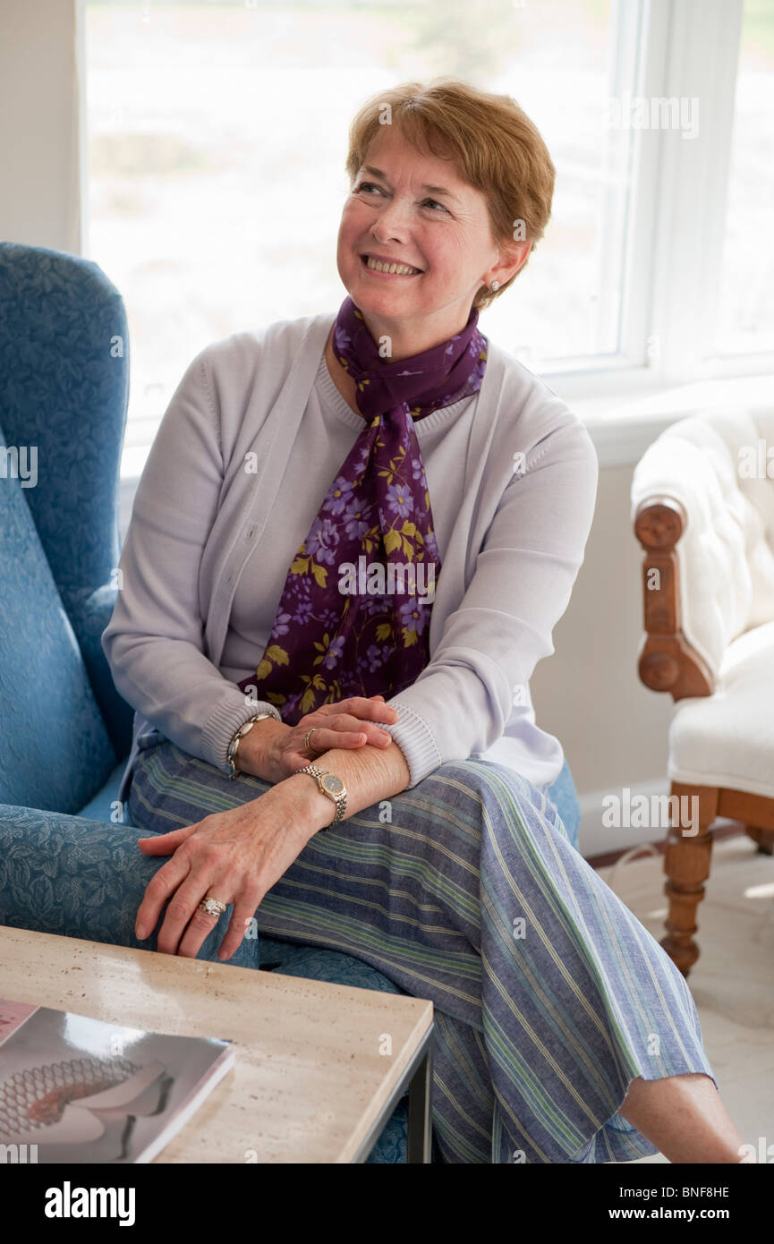 Mature woman smiling in living room - Stock Image