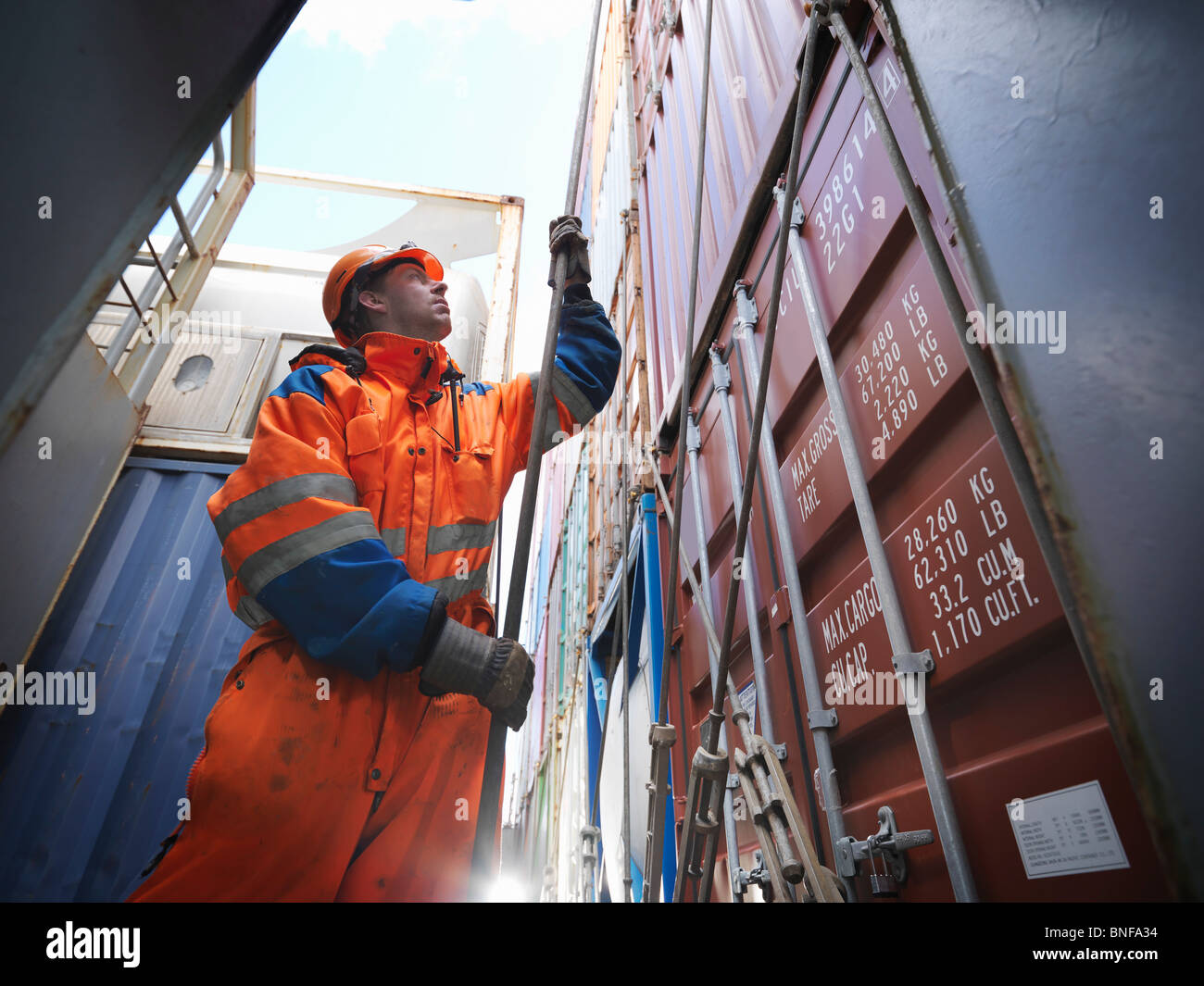Sailor pulling a rope in cargo bay - Stock Image
