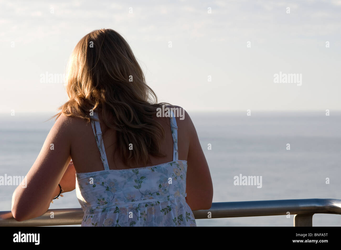 Back view of  woman standing on a balcony looking out at the ocean - Stock Image