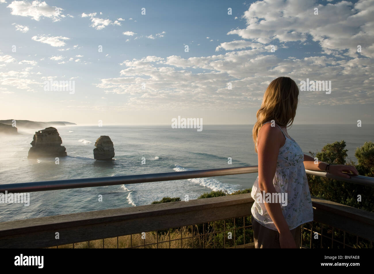 Woman standing on a balcony with the coastline of The Twelve Apostles in the background - Stock Image