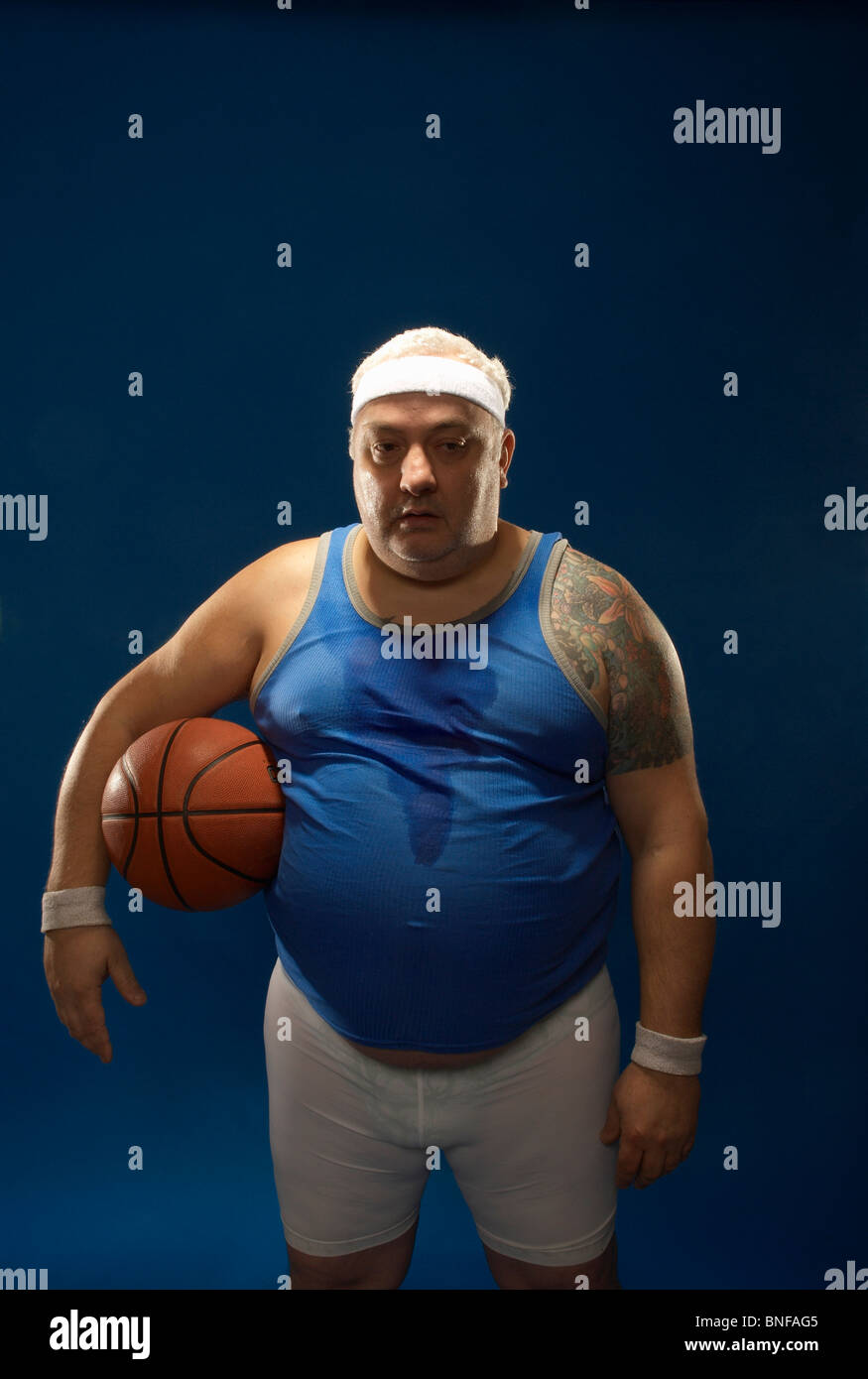 Large sportsman holding basketball - Stock Image