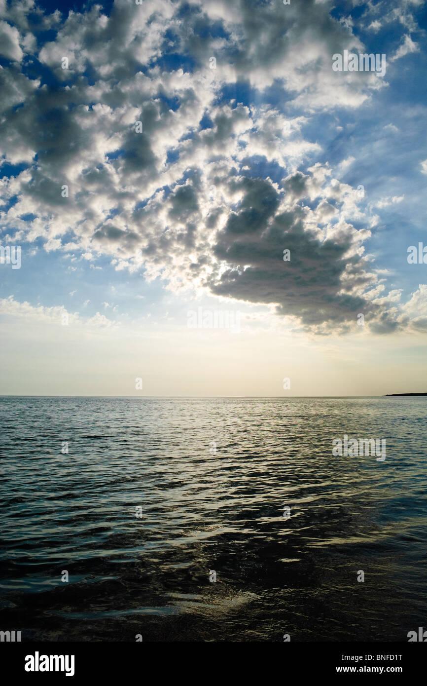 Dark clouds over blue sky above sea - Stock Image