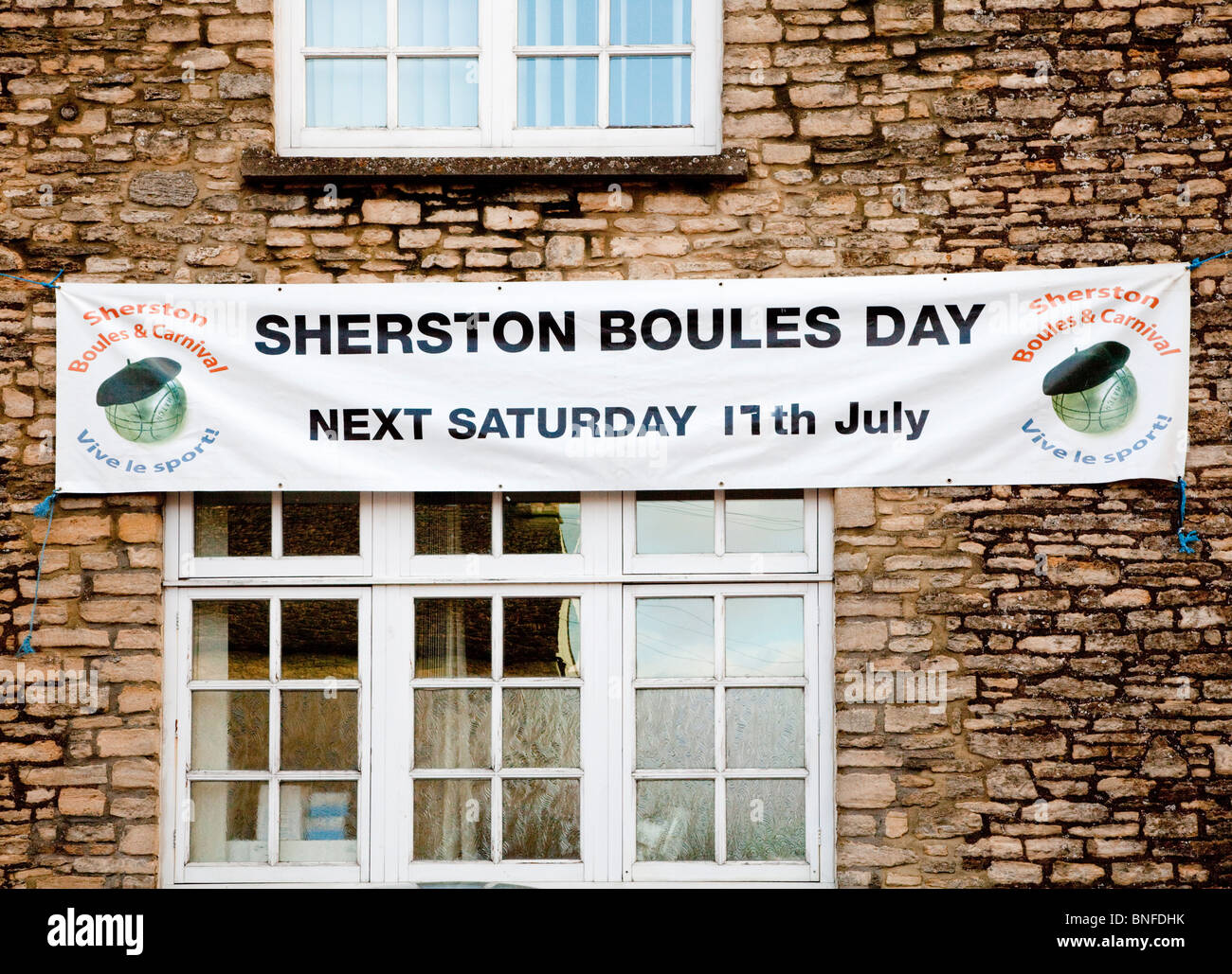 Banner on the Tolsey advertising the annual Boules Day and Carnival in the Cotswold village of Sherston, Wiltshire, - Stock Image