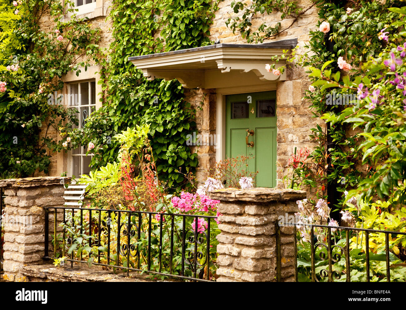 Pretty summer front garden of a typical Cotswold stone house in the Wiltshire village of Sherston, England, UK - Stock Image