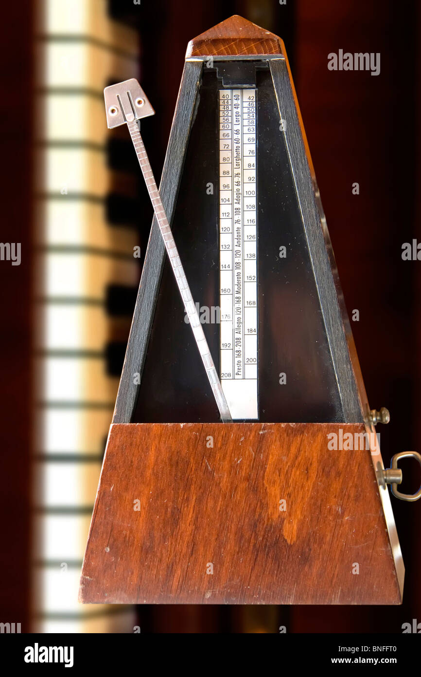 Old metronome over white table with vertical piano behind (vertical photo) - Stock Image