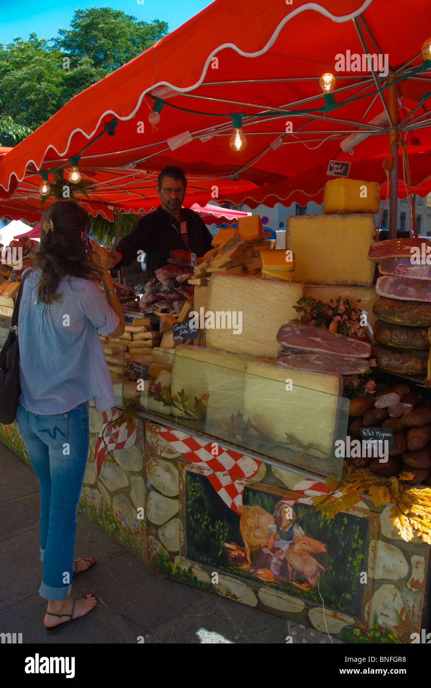 Cheese and meat stall Marche Parmentier street market along Boulevard Richard Lenoir Paris France Europe - Stock Image