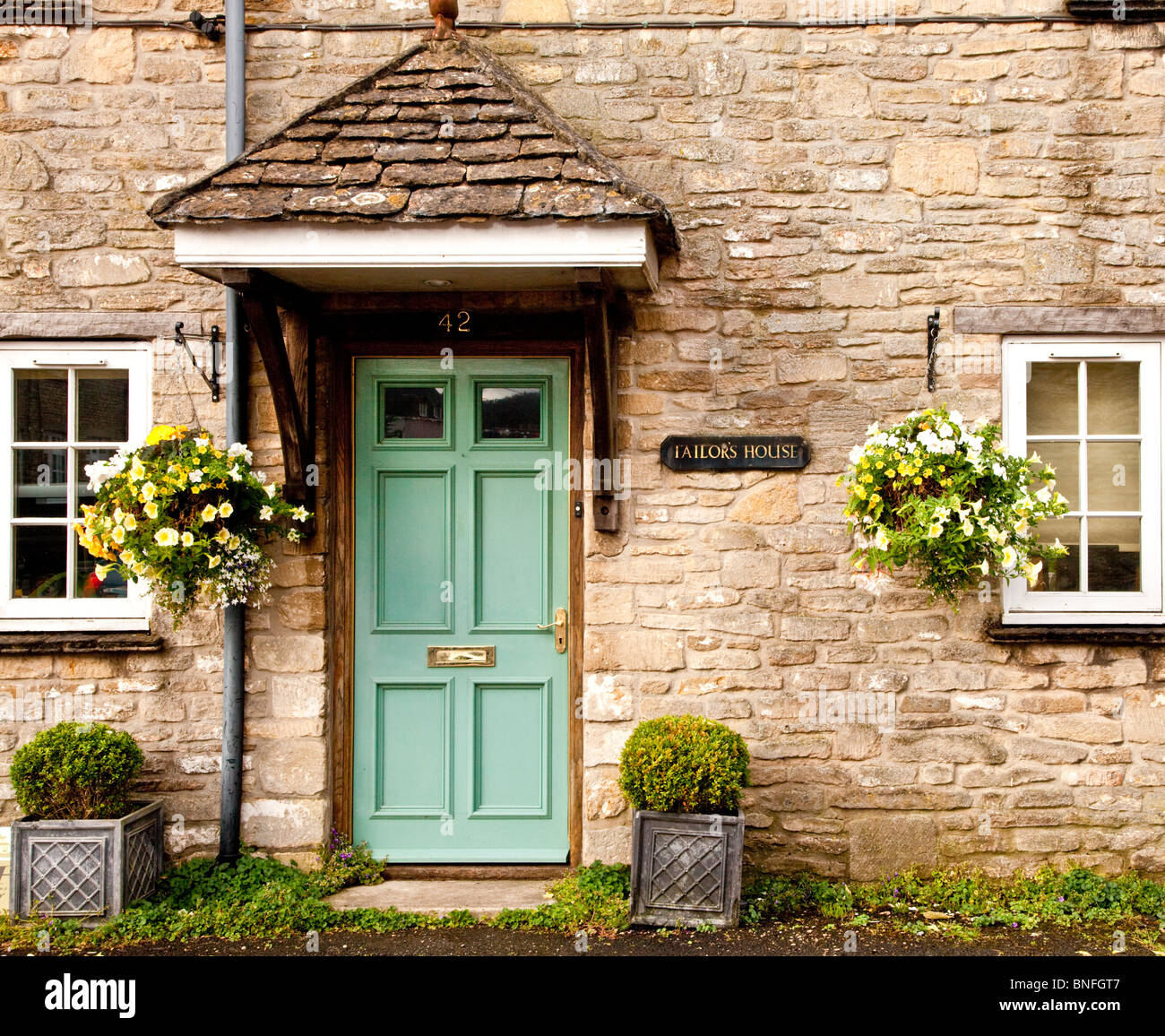 Green wooden front door of an old Cotswold stone cottage in the village of Sherston, Wiltshire, England, UK Stock Photo