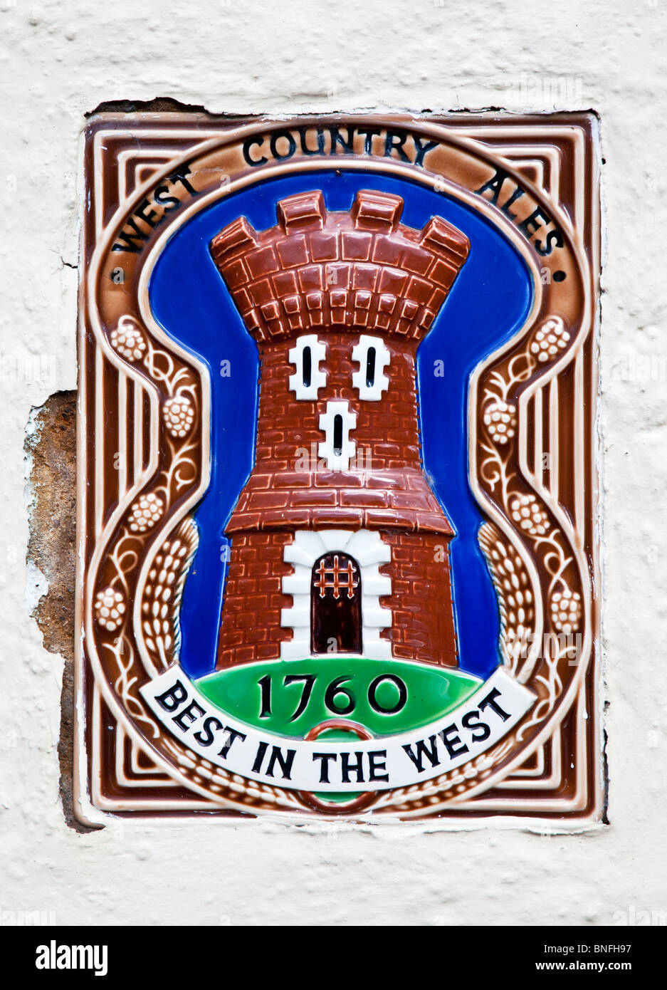 Ceramic wall plaque set into a whitewashed wall advetising a brewery, West Country Ales - Stock Image