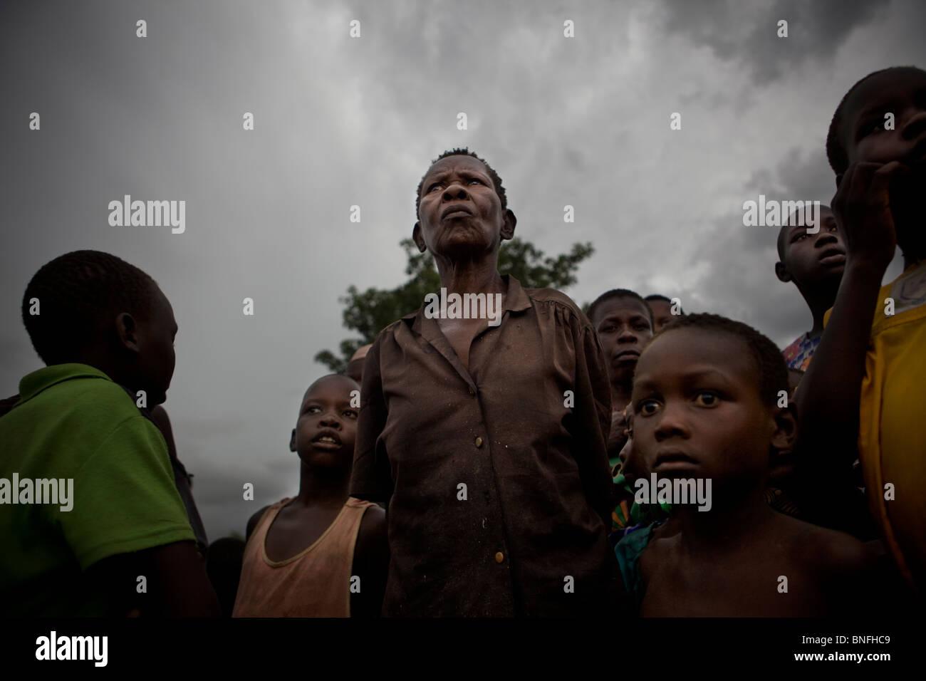 Villagers in northern Uganda under dark skies. - Stock Image