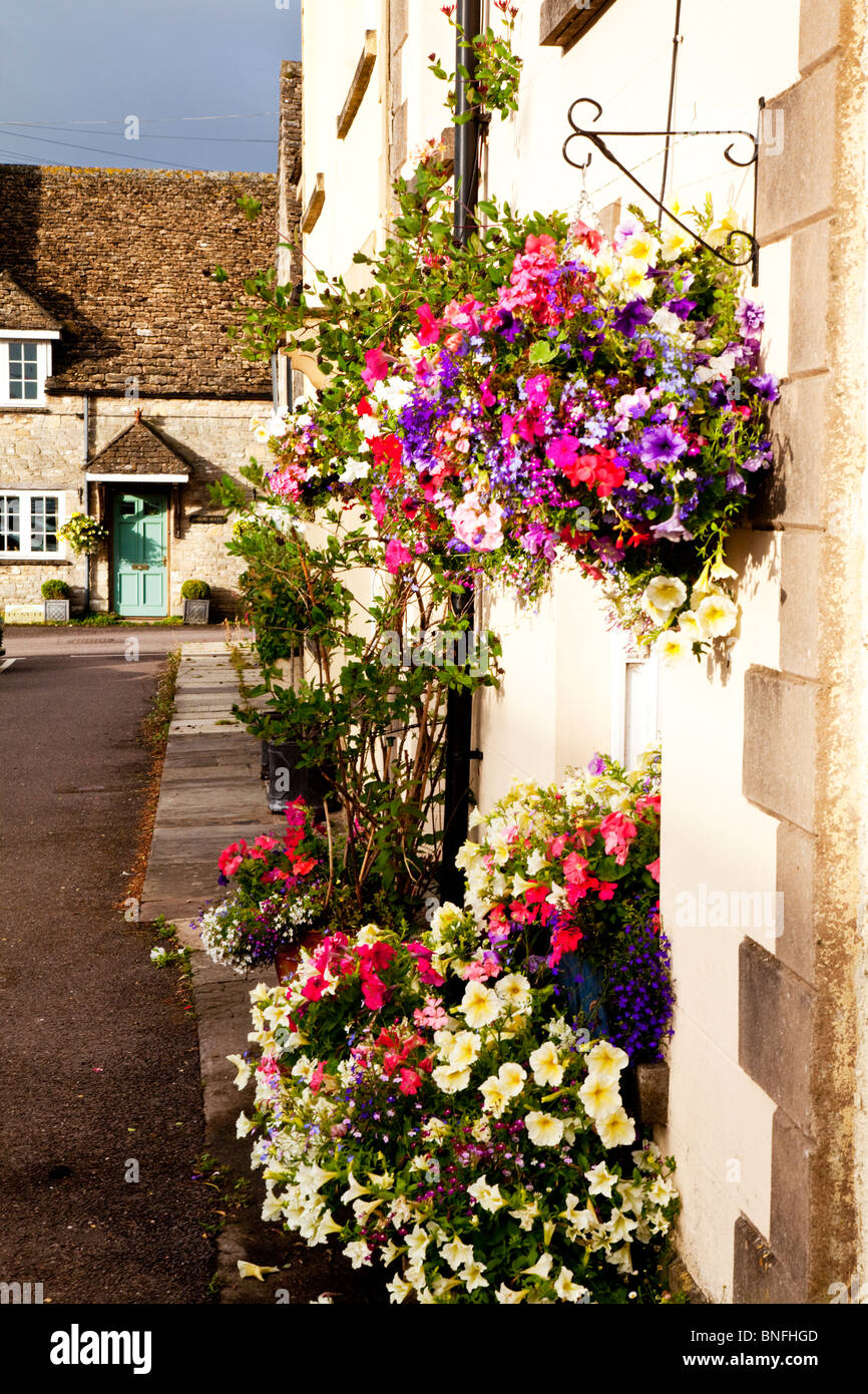 View down Sherston High Street, Wiltshire, to Silver Street. Summer flowers in baskets and containers at the front - Stock Image