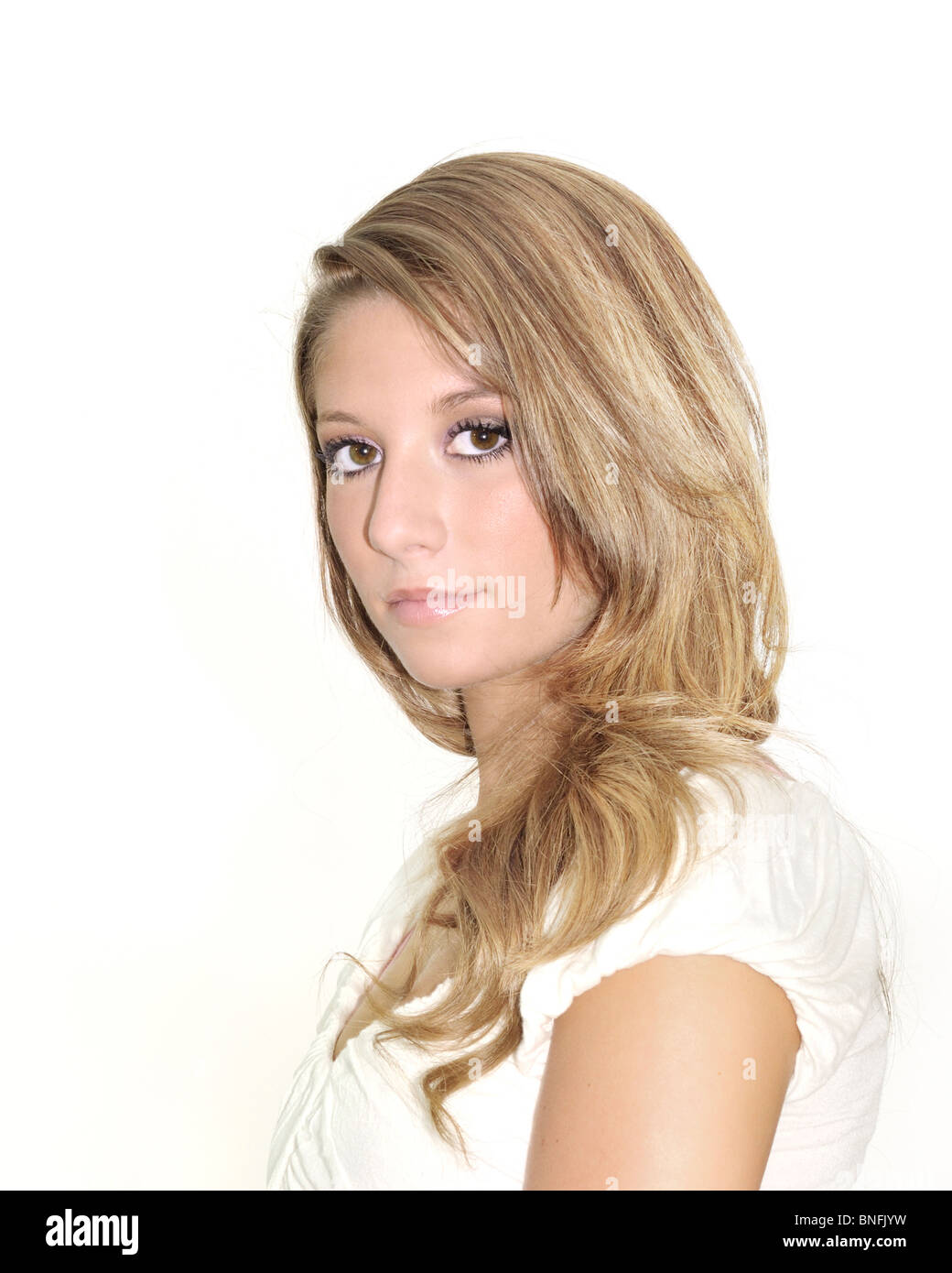 A  closeup high key portrait of a pretty teenage Caucasian girl, white background. - Stock Image