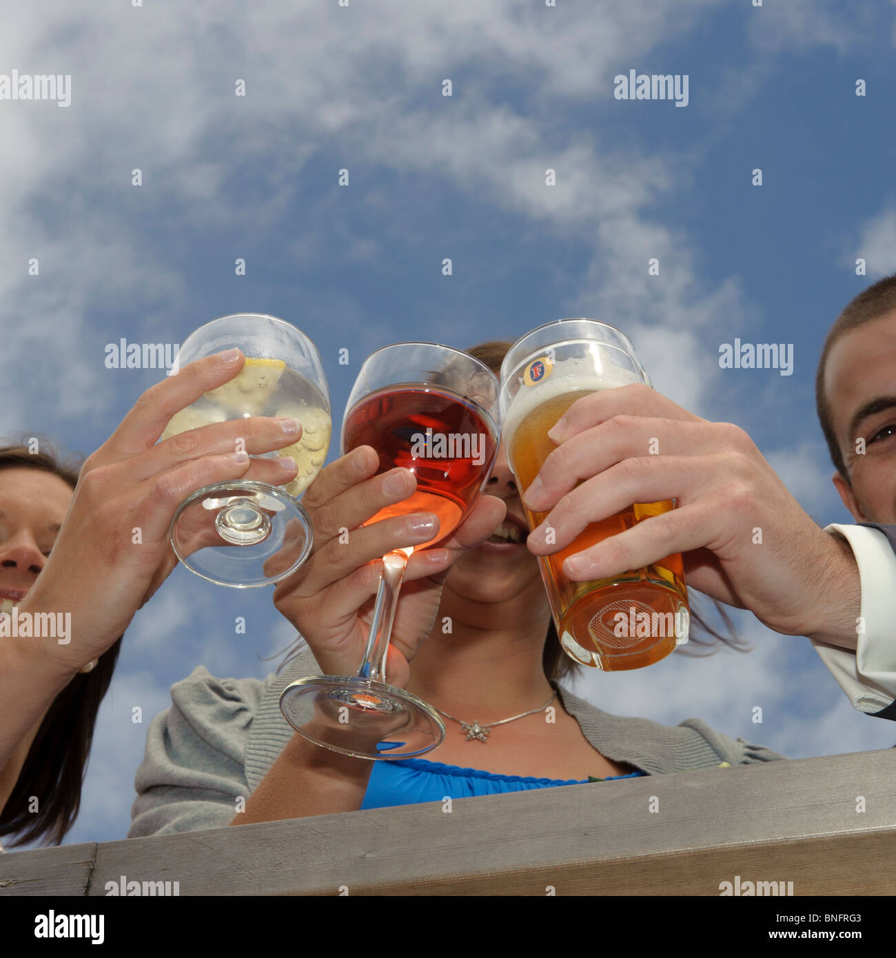Three guests clinking their drinks glasses together at a wedding reception, UK Stock Photo