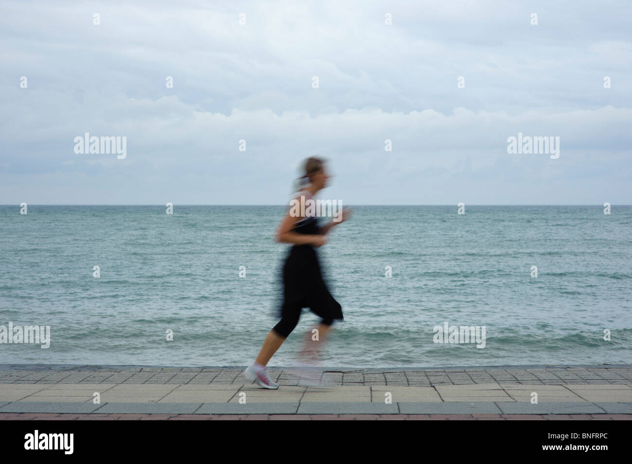 Motion blur, a woman jogger jogging runner running by the sea seaside overcast grey day UK - Stock Image
