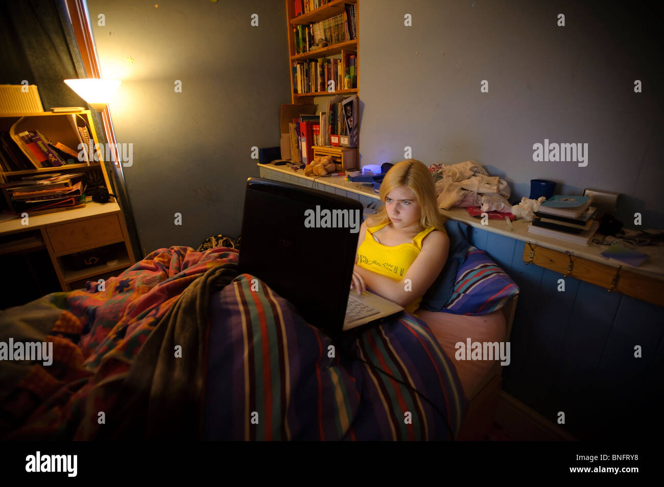a 15 year old teenage girl using her laptop to chat with her Facebook friends online from her bedroom, UK - Stock Image