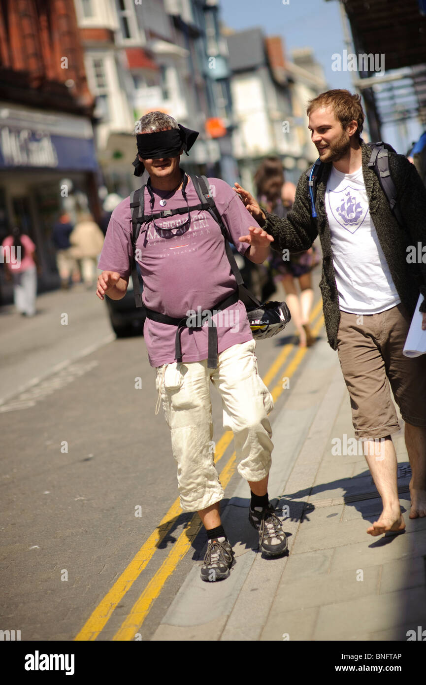 Leading a man wearing a blindfold through the streets of Aberystwyth in an exercise to measure the accessibility - Stock Image