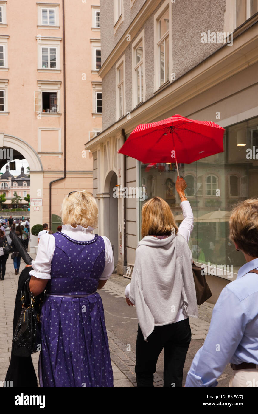 Salzburg, Austria, Europe. Woman tour guide holding a red umbrella high up in historic city. - Stock Image