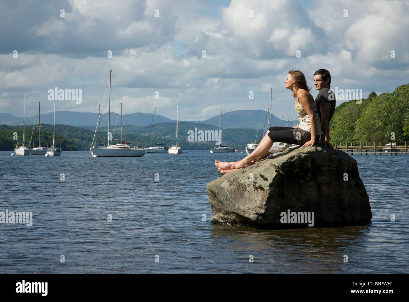 Young couple relaxing at Fell Foot Park, Lake Windermere, Lake District National Park, Cumbria, England UK - Stock Image