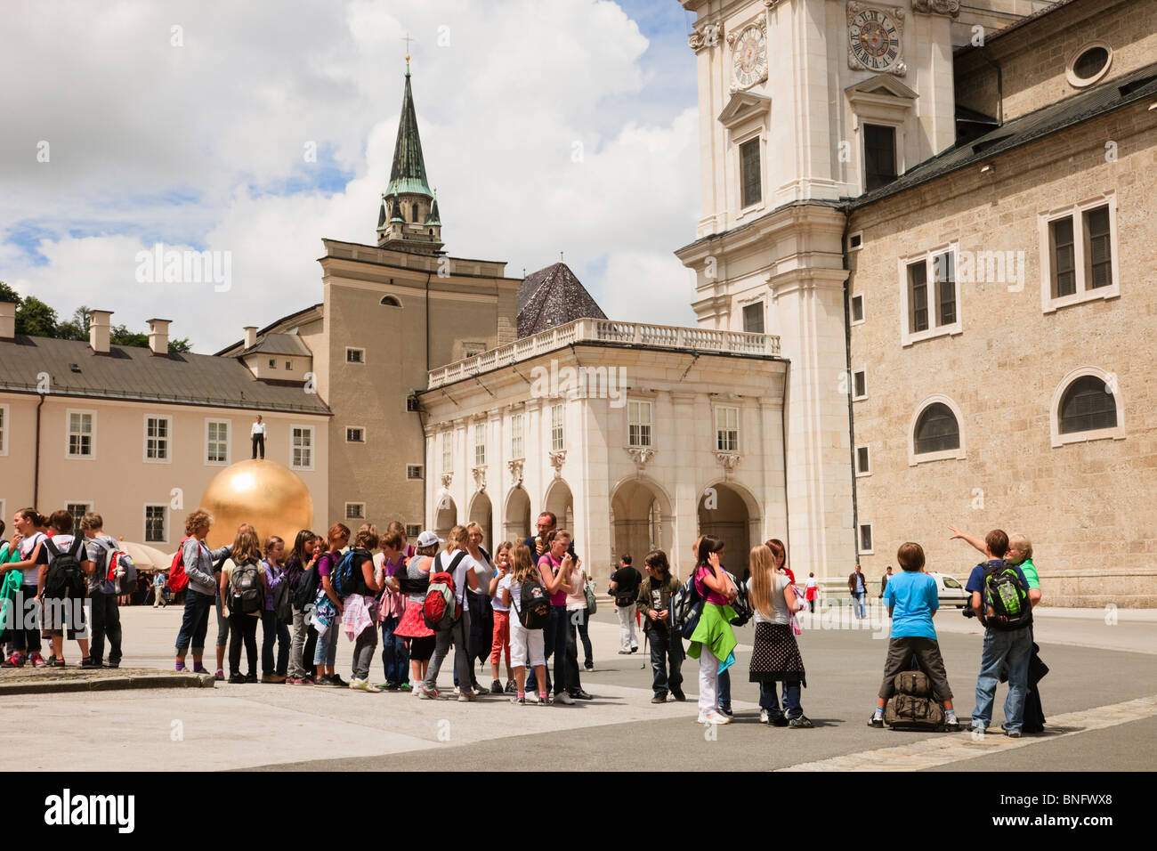 Group of children on a school trip in the historic city square by Dom Cathedral in Kapitel Platz, Salzburg, Austria, - Stock Image