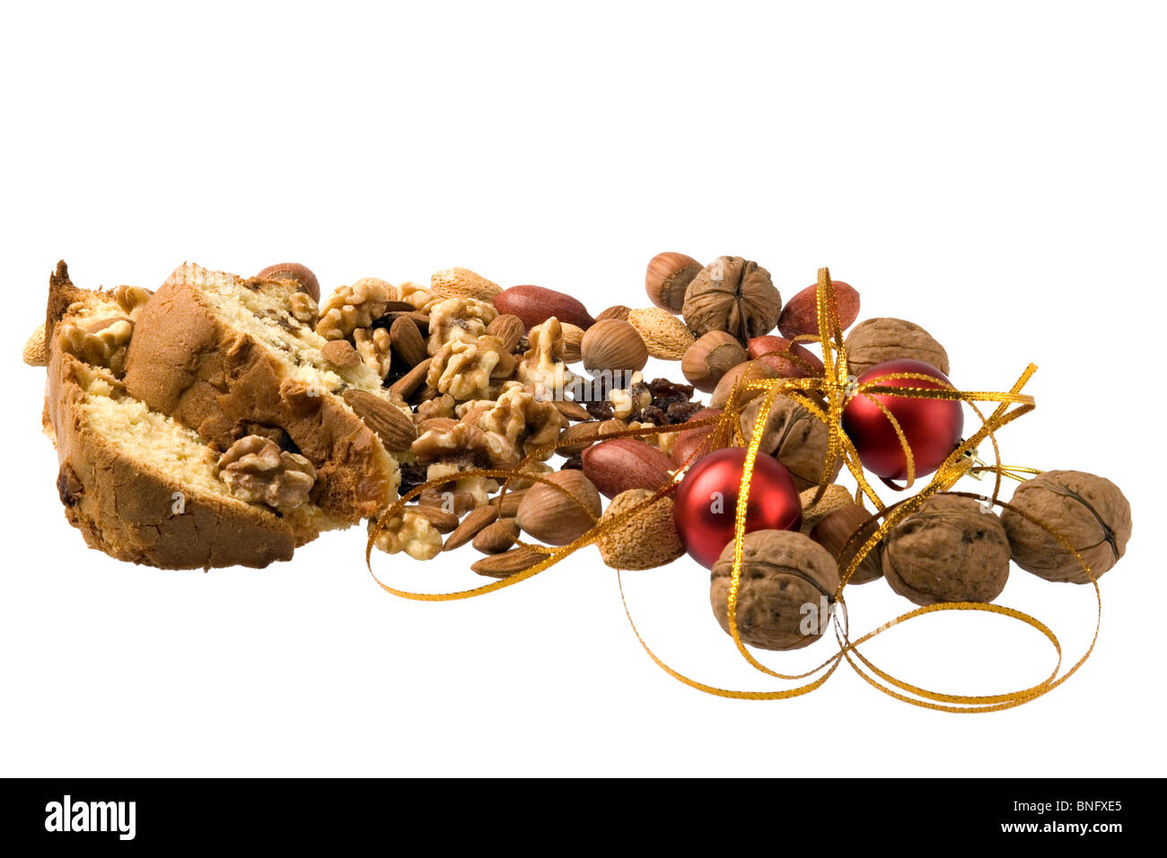 Pieces of christmas cake, nuts, and xmas decoration isolated against white. - Stock Image