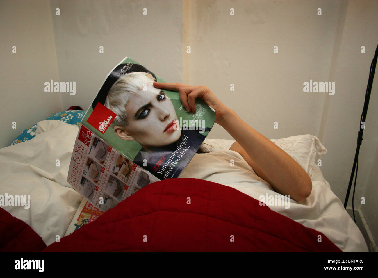 Woman in bed reading a copy of the Observer Woman featuring Agyness Deyn on the front cover, UK. - Stock Image