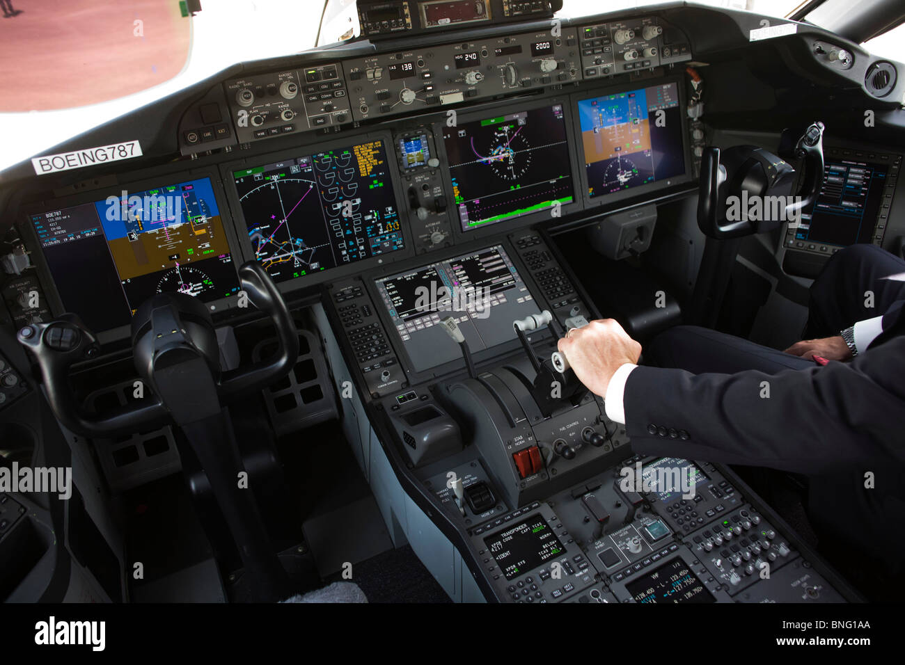 In glass cockpit of LCD screens, Boeing pilot with hands on throttles of 787 dreamliner - Stock Image