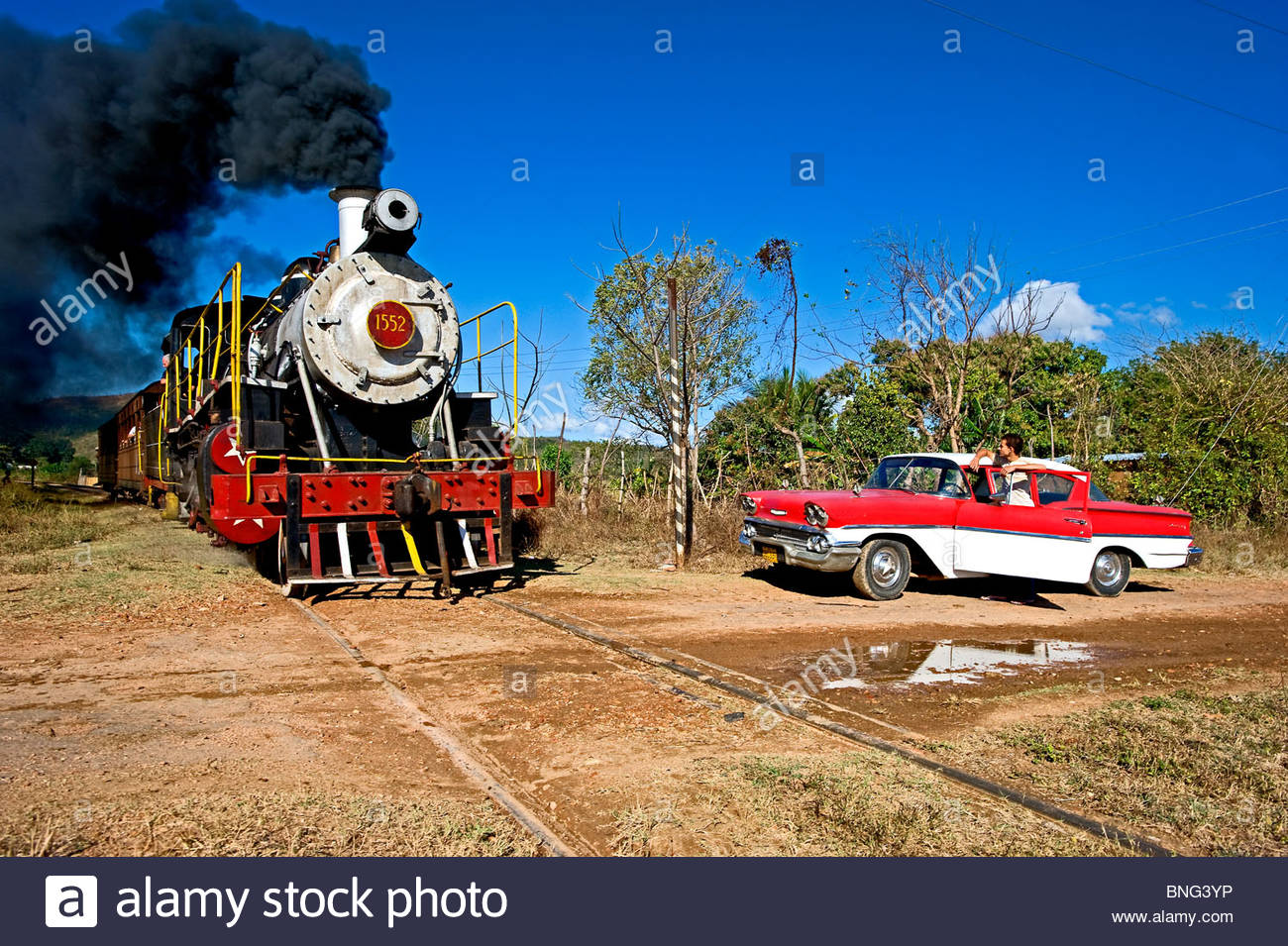 Car of the 50's and steam train in La Pastora,Cuba - Stock Image