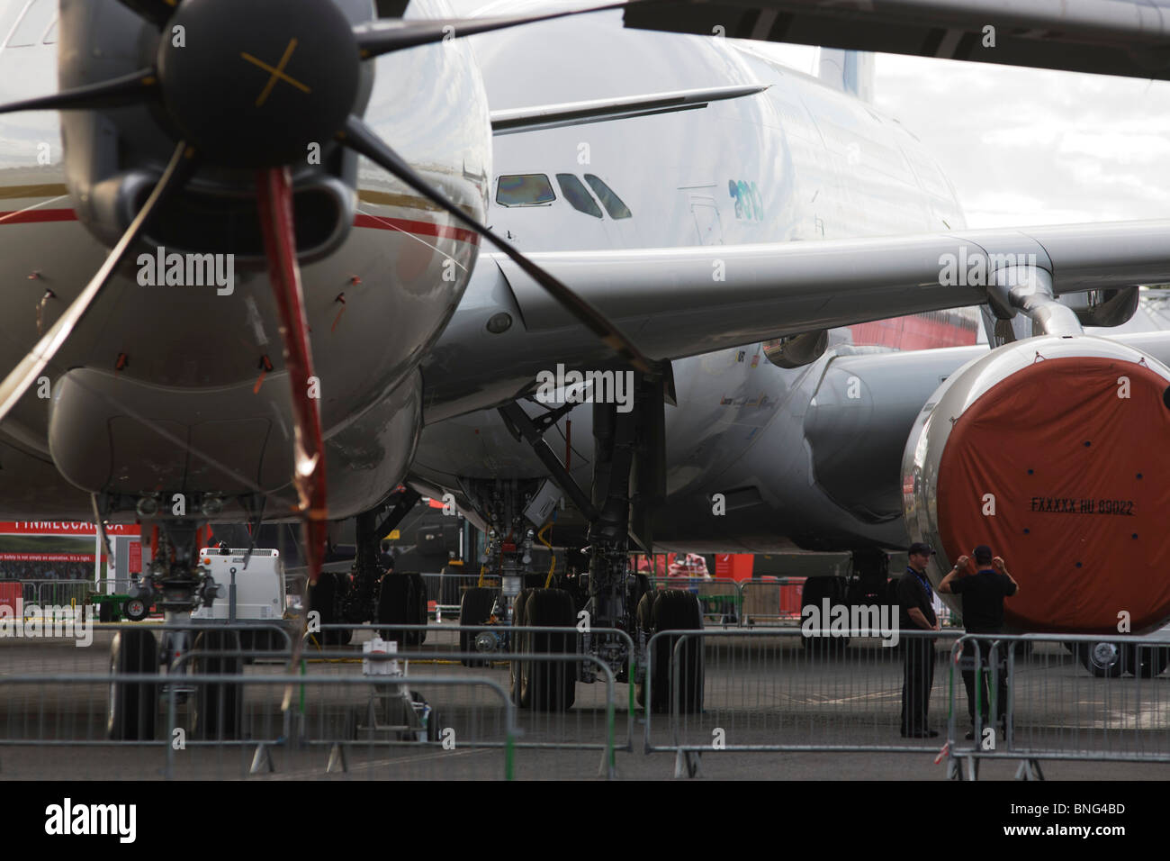 Security staff and static display aircraft lined-up at the Farnborough Airshow, the A380 at the back and a 777 in Stock Photo