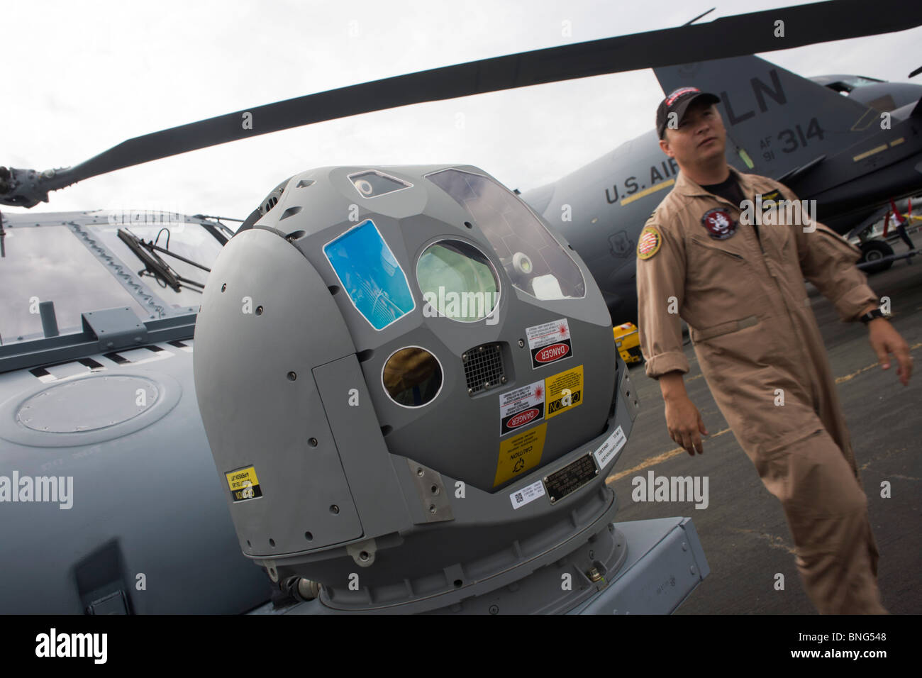 US Navy pilot and infra-red imaging camera on nose of a Sikorsky MH-60R helicopter at the Farnborough Airshow. - Stock Image