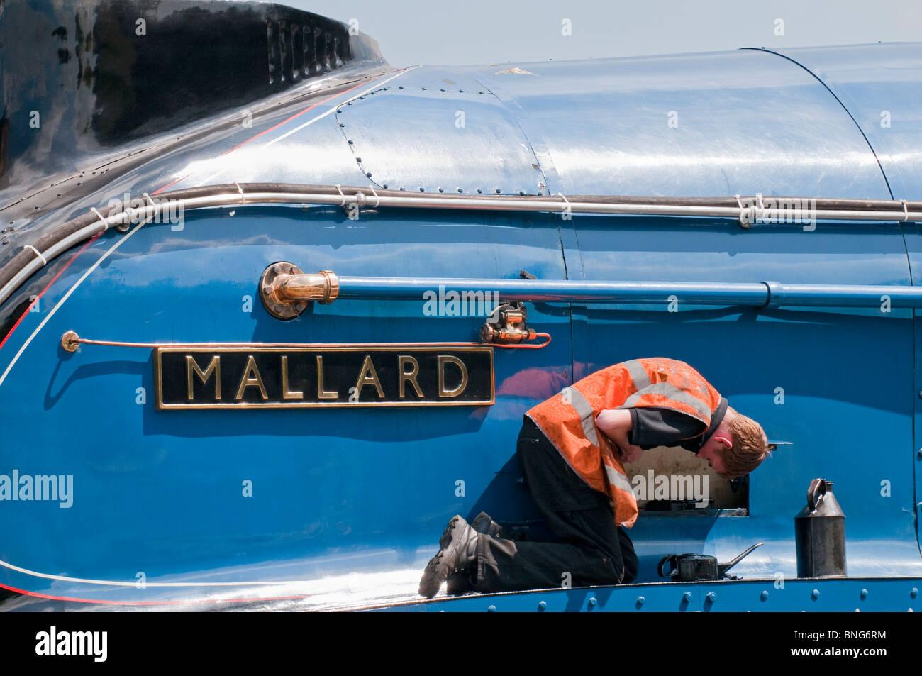 Workman carrying out maintenance checks on the Mallard steam train. - Stock Image