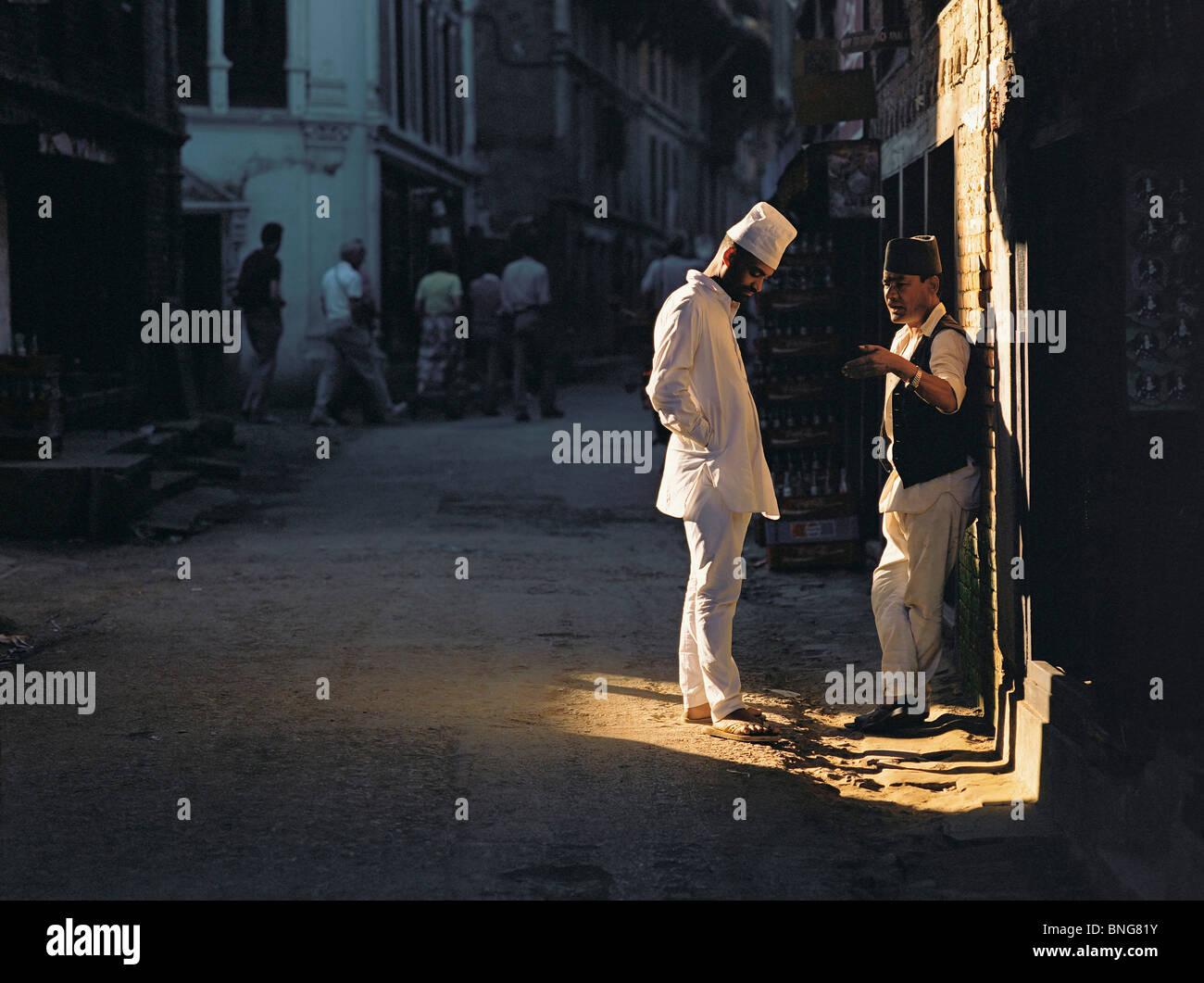 Two men chat in a patch of sunlight in a Kathmandu backstreet, Kathmandu, Nepal - Stock Image
