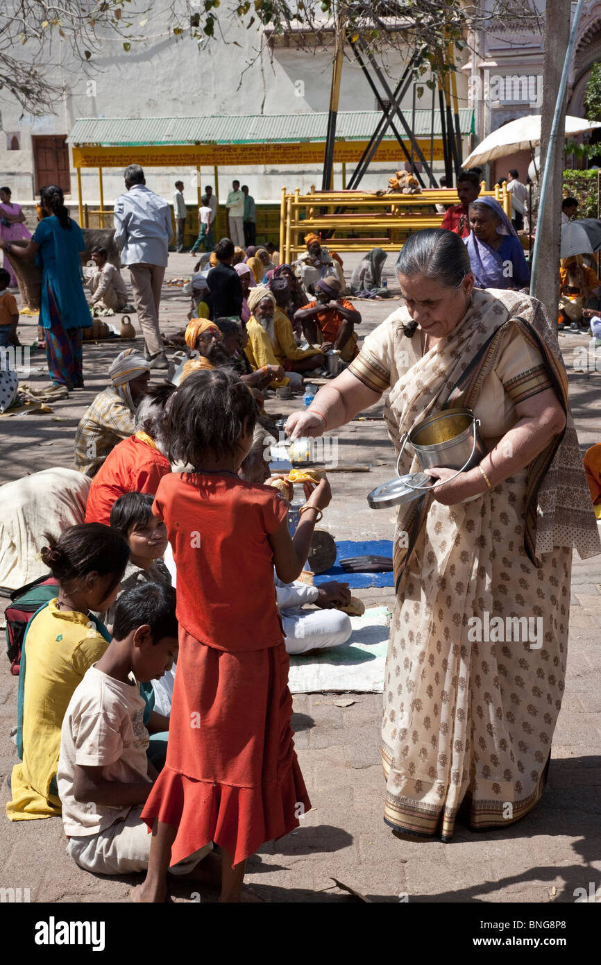 Woman giving food to beggars. Orchha. India - Stock Image
