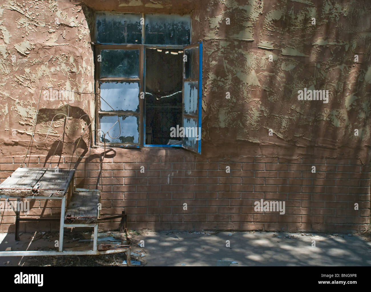 Junk left outside an abandoned building surprisingly provides a peaceful setting. - Stock Image