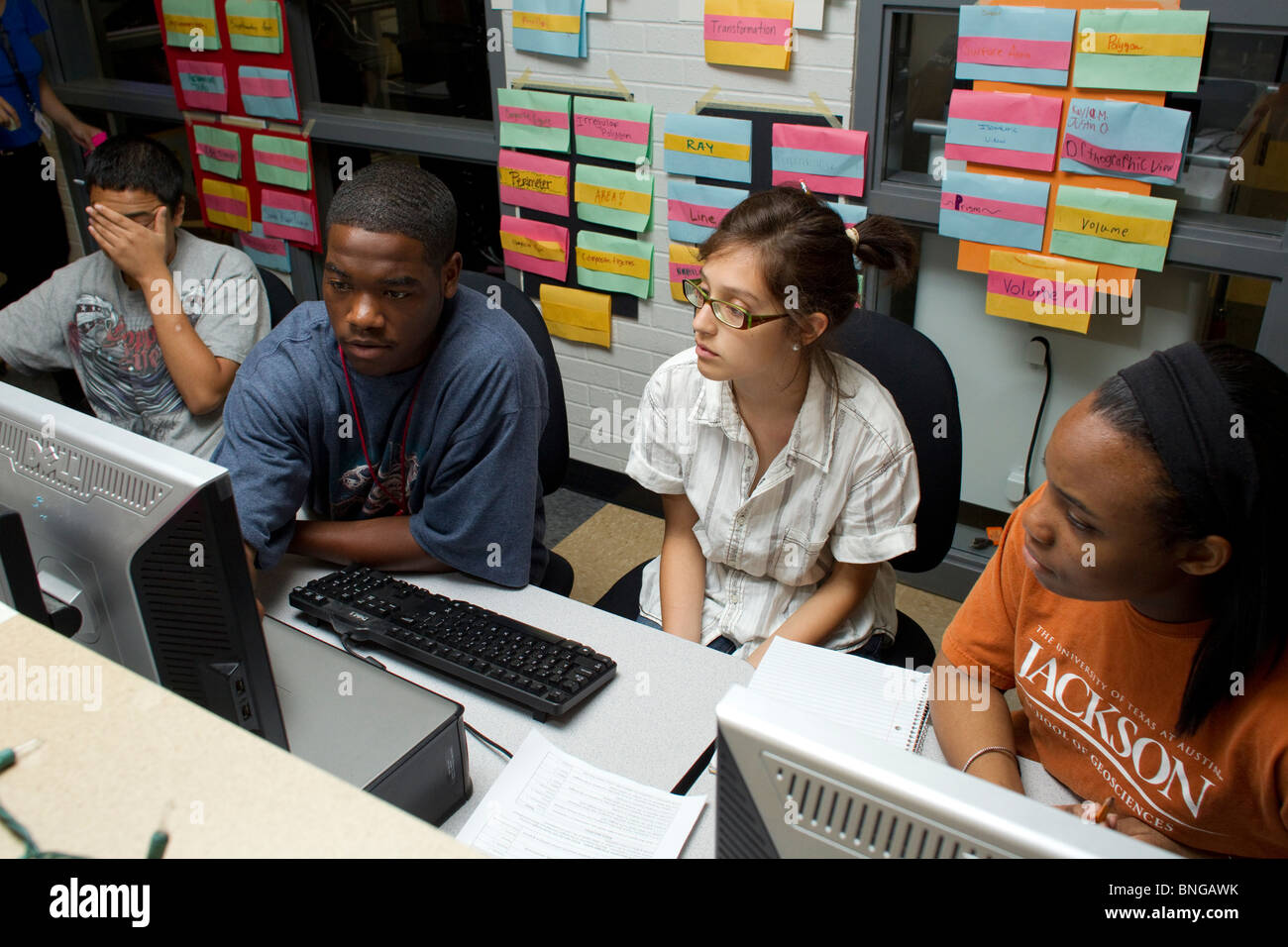 Multi-ethnic group of high school students use computers to work on project together in physics class at Manor New - Stock Image