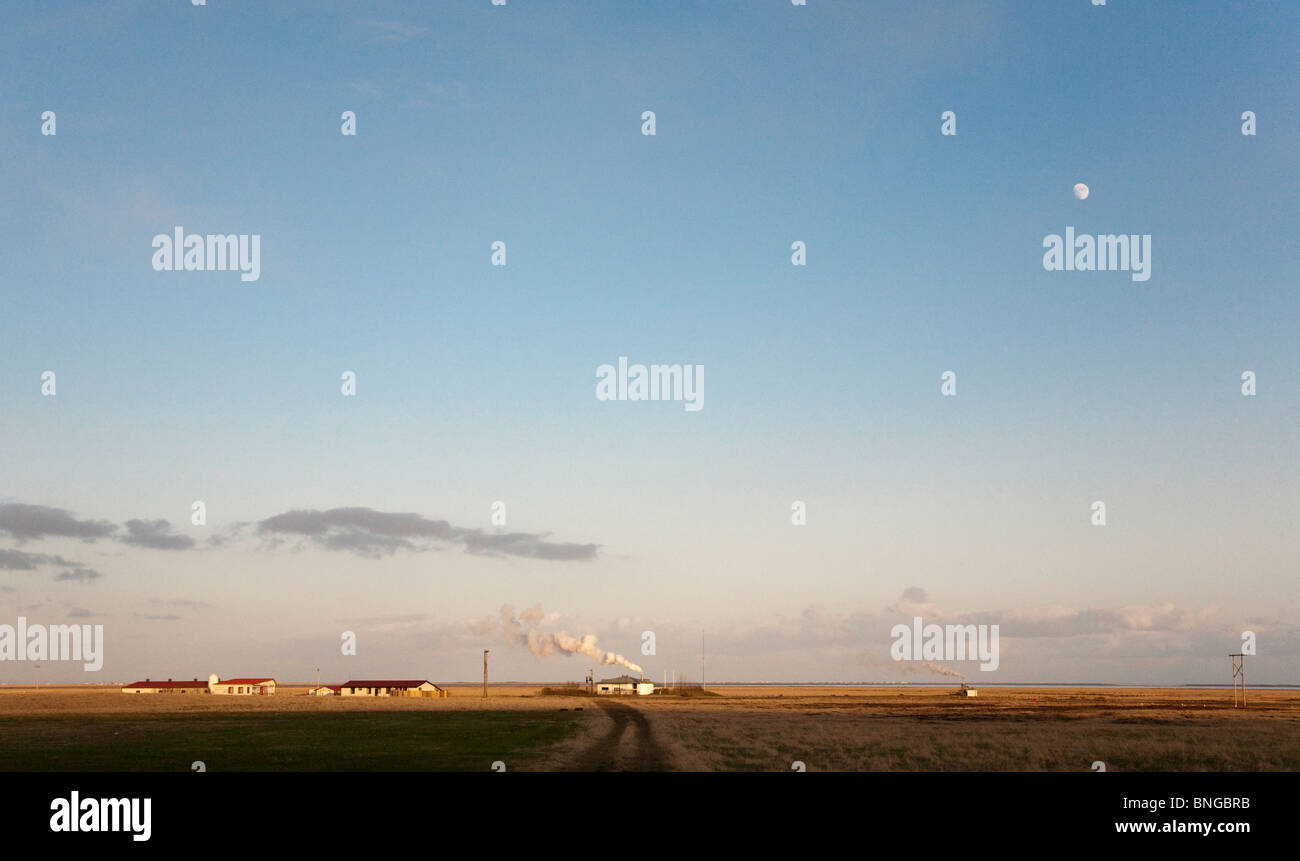 Farm, steam vents and moon, SW Iceland - Stock Image