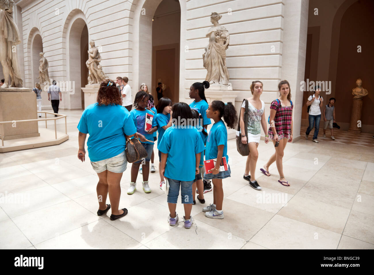 group of schoolgirls wearing identical bright blue tee shirts on a summer outing to the Metropolitan museum of Art - Stock Image