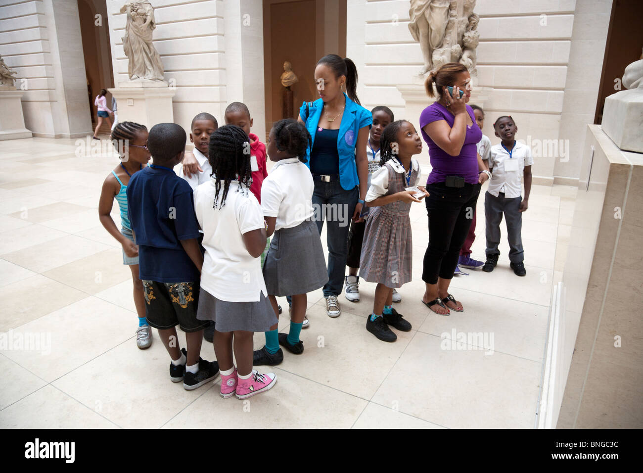 group of small black schoolchildren in the Petrie Court of the Metropolitan Museum of Art on a summer outing with - Stock Image