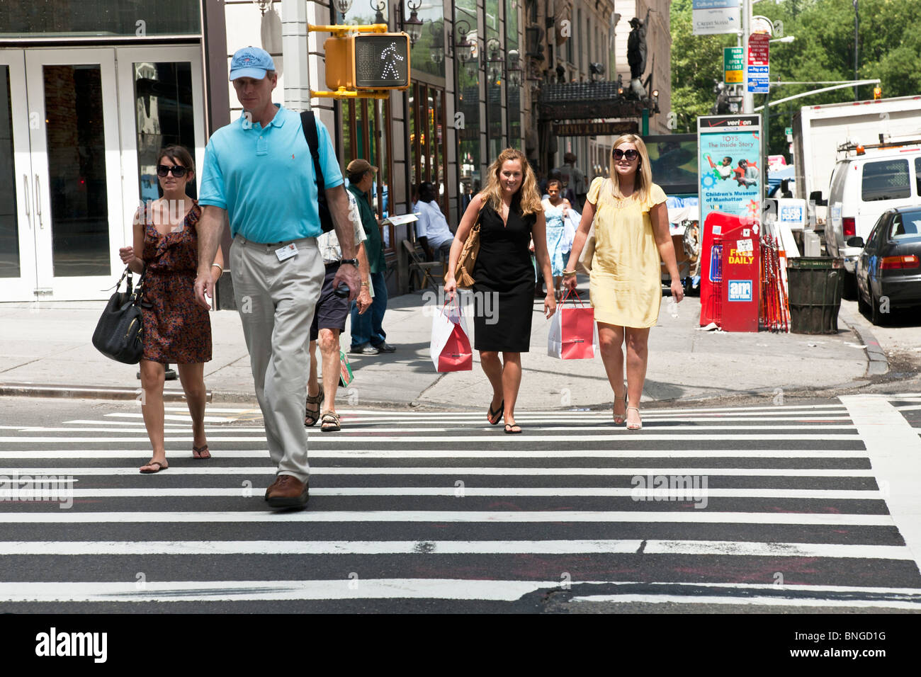 pedestrians including two pretty girlfriends in summer dresses carrying identical shopping bags cross 57th Street - Stock Image