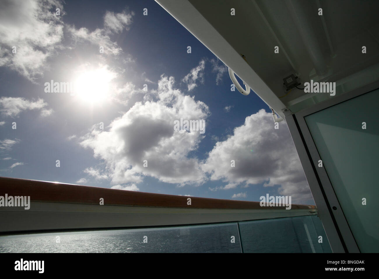 view from balcony of cruise ship looking at sky with sun shinning through clouds - Stock Image