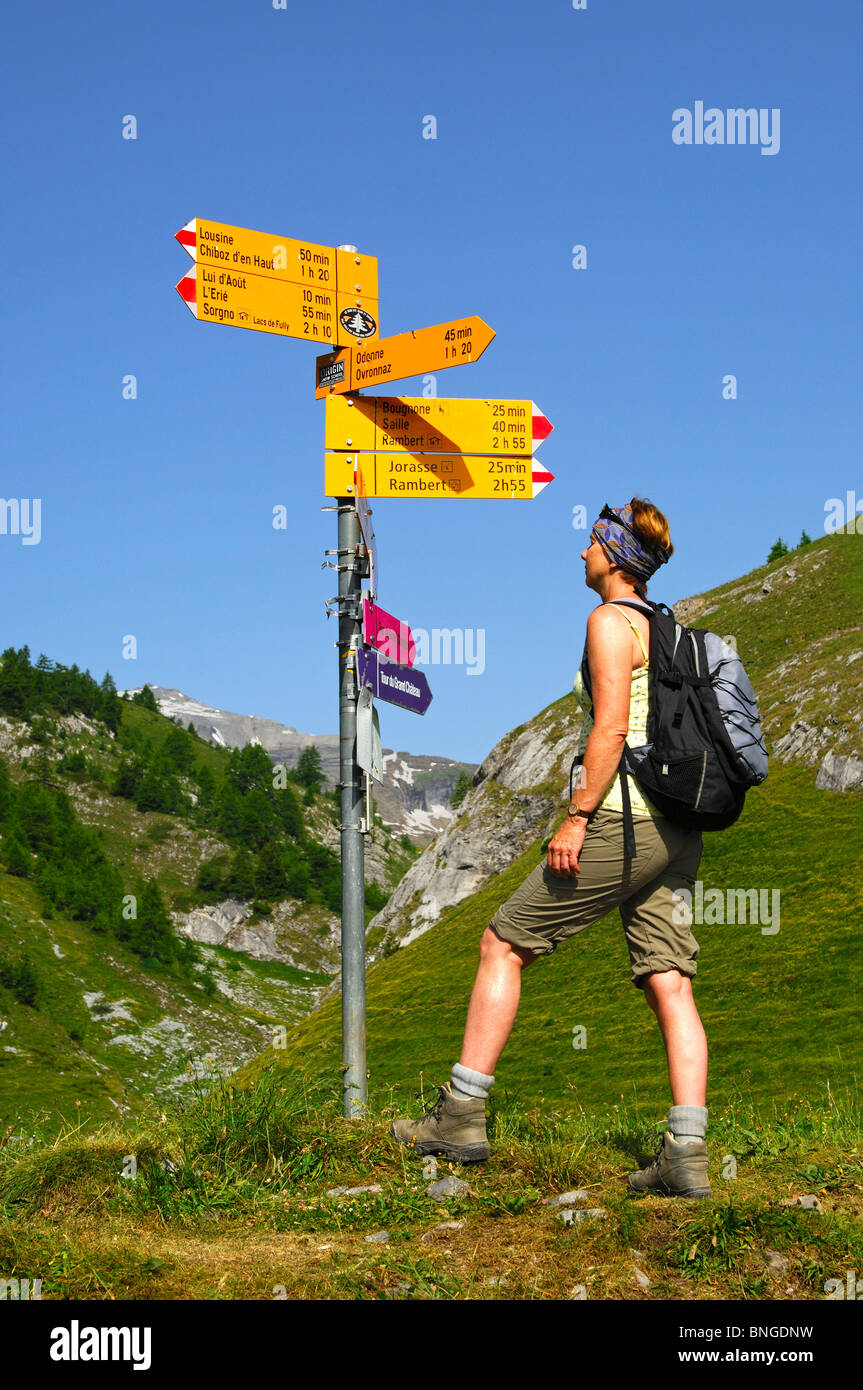 Hiker reading a directional sign at a crossroads on the alp Petit Pre in the hiking area of Ovronnaz, Valais, Switzerland - Stock Image