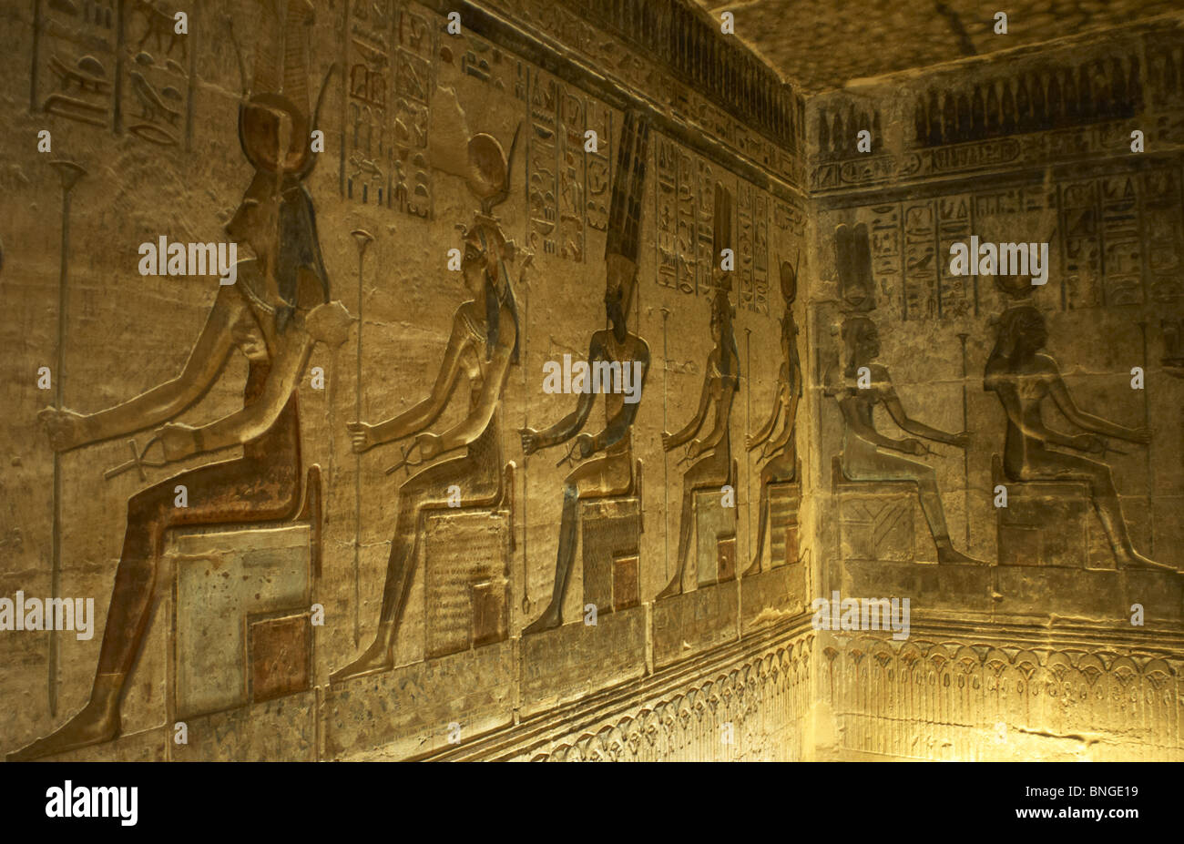 Ptolemaic temple of Hathor and Maat. Polychrome reliefs that decorate the interior. Seated gods. Deir el-Medina. Stock Photo