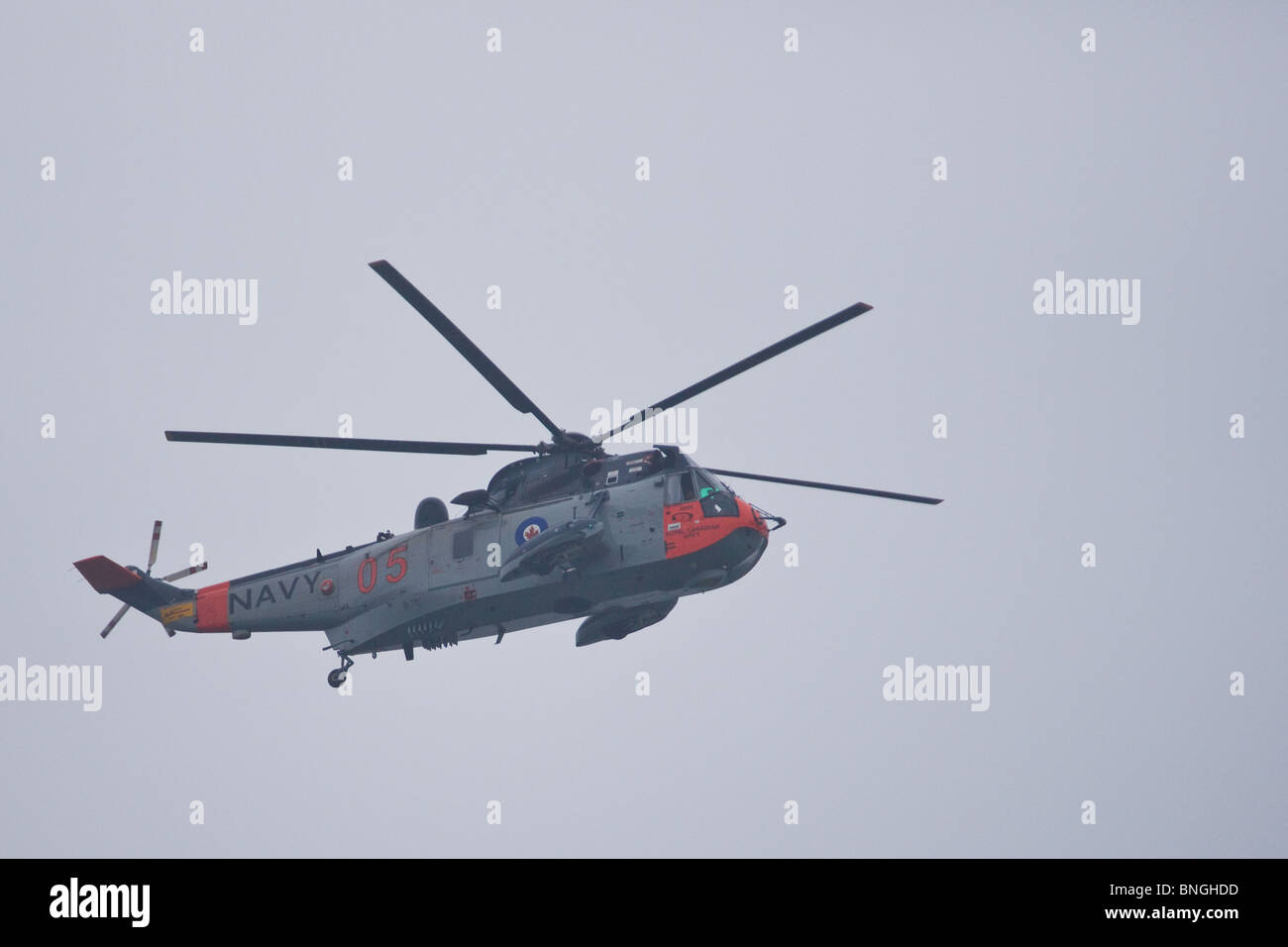 A Sea King helicopter painted in the original Royal Canadian Navy scheme flies overhead during the 2010 Fleet Review. - Stock Image