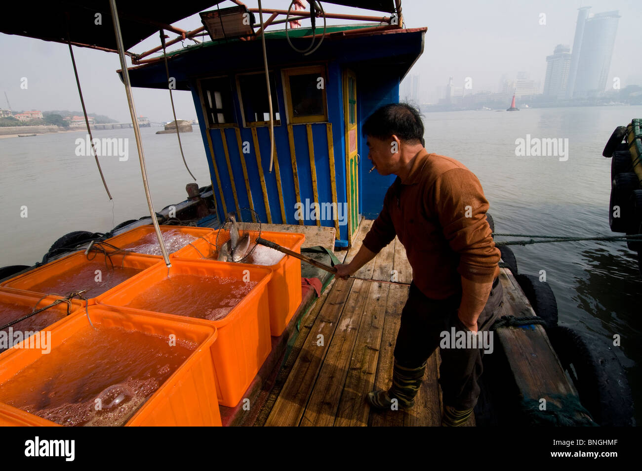 A fisherman on his boat in Xiamen, China - Stock Image