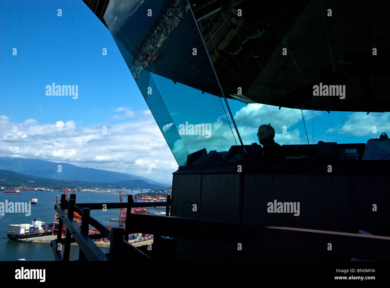 Controller in glass enclosed Vancouver Harbour Tower world's highest air traffic control atop roof of Sun Province - Stock Image